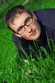 Young man in glasses is liyng in green grass — Stockfoto