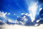 Blue cloudy sky and bright sun beams — Stock Photo