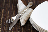 Fork knife and empty plates on the background of brown material — Stock Photo