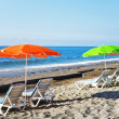Parasols and deck chairs on a sandy beach — Stock Photo