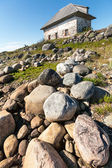Stone house on the rocky shore. — Stock Photo