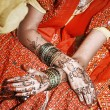 Hands of young Indiwomadorned with traditional bangles and mehndi. — Stock Photo #19495573