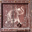 Old wooden door with a picture of an elephant. Fragment.  — Stock Photo