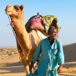 Camel man leads his camel across the Thar desert  — Stock Photo