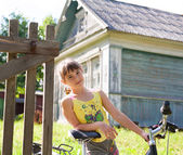 Girl with a bicycle against a village house — Stock Photo