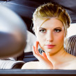 Young woman looking in rear view mirror car — Stock Photo
