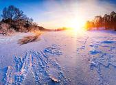 Sunrise over the frozen river - winter landscape — Stock Photo