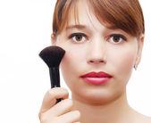 Young beautiful woman using a make-up brush — Stock Photo