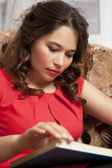 Woman looking away while sitting on a sofa in a living room — Stock Photo
