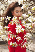 Beautiful girl in the red dress. Blossoming apple — Stock Photo