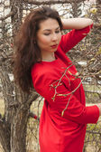 Beautiful girl in the red dress. Blossoming apple — Стоковое фото