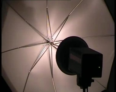 Flashing photo studio strobe with umbrella