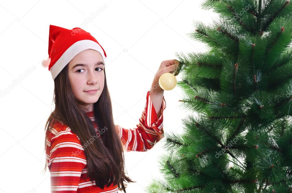 Young girl wearing beanie decorating christmas tree, eye contact, horizontal shot — Stock Photo #14705685