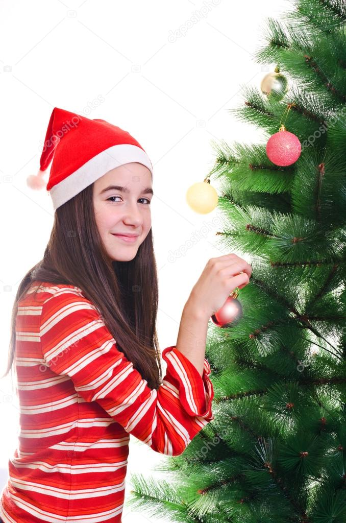 Young girl wearing beanie decorating christmas tree, eye contact, vertical shot — Stock Photo #14705701