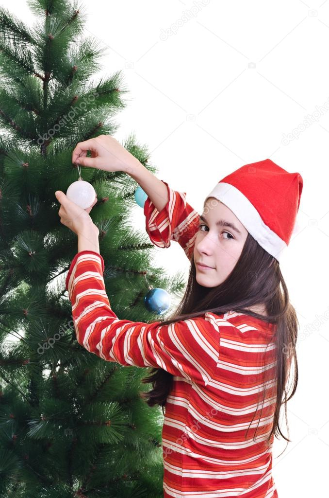 Young girl wearing beanie decorating christmas tree, eye contact, vertical shot — Stock Photo #14705717