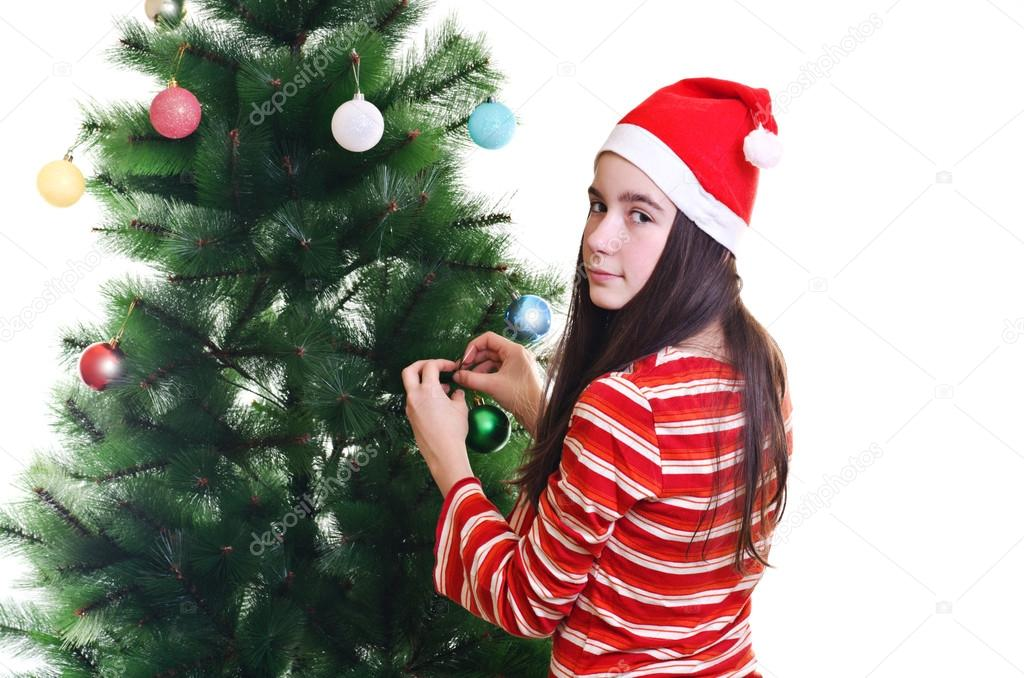 Young girl wearing beanie decorating christmas tree, eye contact, horizontal shot — Stock Photo #14705745