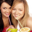 Blonde and the brunette drink juice — Stock Photo #2269693