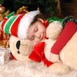 Girl - the Christmas elf sleeps under a fir-tree - Stock Photo