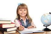 Niña se sienta en una mesa y escribe en cuadernos — Foto de Stock