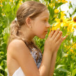 Stock Photo: Girl in garden smells yellow flower