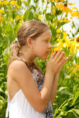 Girl in garden smells yellow flower — Stock Photo