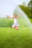 Girl jumps under spray drops — Stock Photo