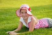 Cute little girl lying on grass — Stock Photo