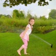Little girl runs in park under water splashes — Stock Photo