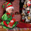 Girl Christmas elf with gift near Xmas fir-tree — Stok fotoğraf