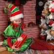 Girl Christmas elf with gift near Xmas fir-tree — Stock Photo
