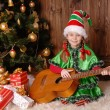 Girl - the Christmas elf with a guitar — Stock Photo