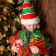 Girl in suit of Christmas elf with a gift — Stock Photo