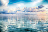 Beautiful clouds above ocean at sunrise — Stock Photo