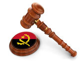 Wooden Mallet and Angola flag — Stock Photo