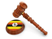 Wooden Mallet and Uganda flag — Stock Photo