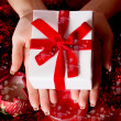 Hands holding red Christmas gift — 图库照片