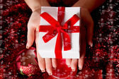 Hands holding red Christmas gift — Stock Photo