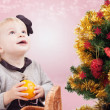 Surprised little girl under Christmas tree — Stock fotografie