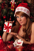 Santa helper with present under Christmas tree — Stock Photo