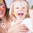 Mother and daughter with paint on faces — Stock Photo #12760534