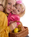 Mother and baby daughter with basket of apples — Stock Photo