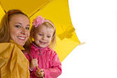 Mother and baby daughter under yellow umbrella — Stock Photo
