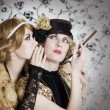 Two retro styled women sharing secrets - ストック写真