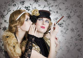 Two retro styled women sharing secrets — Stockfoto