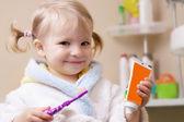 Menina sorridente com escova de dentes e tubo — Foto Stock
