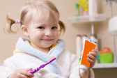 Smiling girl with toothbrush and tube — Стоковое фото