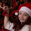 Smiling woman in Santa hat with bell - Stock Photo