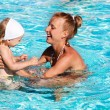 Happy kid playing with mother in swimming pool — Stockfoto
