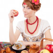 Stock Photo: Russiwomeating apples at table