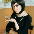 Retro styled woman with glass of cognac — Stock Photo